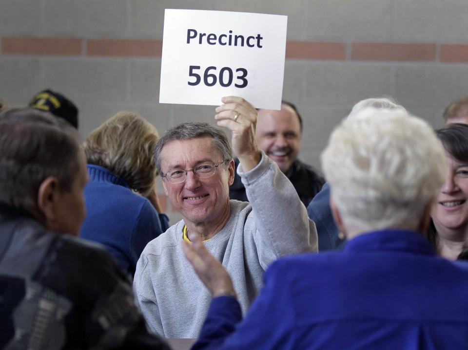 Gary Reed holds up a precinct number sign before the start of caucusing at a high school caucus site, Saturday, Feb. 4, 2012, in Las Vegas.  (AP Photo/Julie Jacobson)