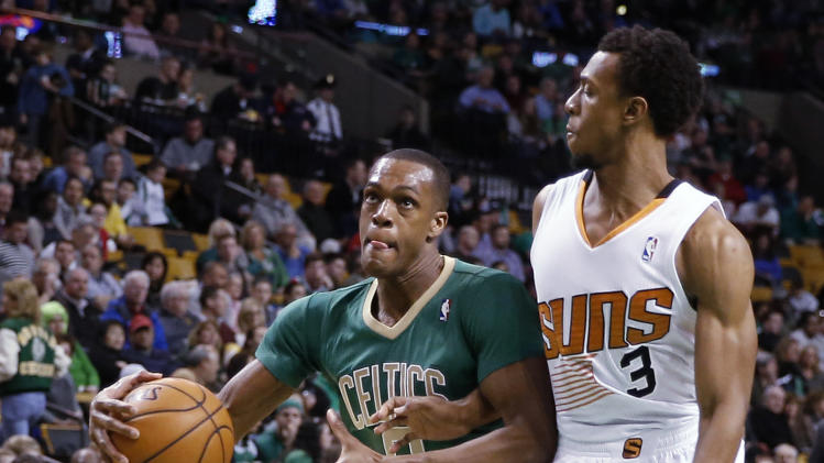 Boston Celtics' Rajon Rondo drives on Phoenix Suns' Ish Smith (3) during the first quarter of an NBA basketball game in Boston on Friday, March 14, 2014. (AP Photo/Winslow Townson)