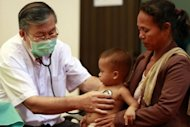 A doctor is seen checking a child at Kantha Bopha children's hospital in Phnom Penh. Health experts working to identify an illness that has killed dozens of children in Cambodia found a link to a virus that causes hand, foot and mouth disease, the UN health agency said on Monday