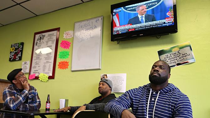 David Johnson, left, Mark Taylor and Charles Strozier watch as U.S. Attorney General Eric Holder makes a televised announcement, Wednesday, March 4, 2015, in Ferguson, Mo. The Justice Department cleared a white former Ferguson police officer in the fatal shooting of an unarmed black 18-year-old, but also issued a scathing report calling for sweeping changes in city law enforcement practices it called discriminatory and unconstitutional. (AP Photo/St. Louis Post-Dispatch, David Carson)