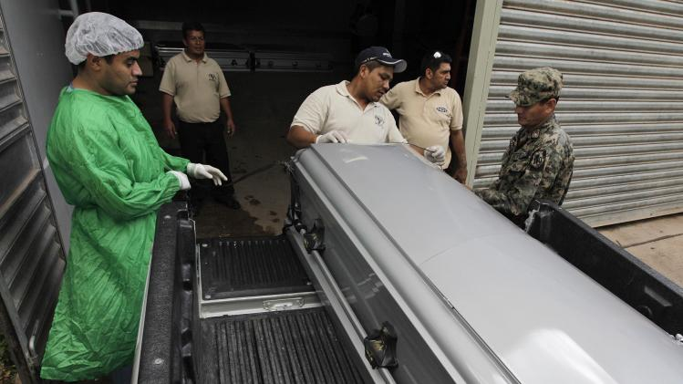 A forensic technician chats with a soldier while receiving a coffin containing the body of a Honduran man that was repatriated from Mexico, at the morgue in Tegucigalpa