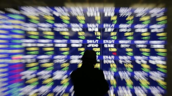 A man looks at at an electronic stock quotation board outside a brokerage in Tokyo