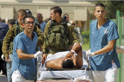 Israeli medics evacuate a person wounded in one of several attacks in the Arava desert, to the Soroka hospitan in Beersheba, southern Israel, Thursday, Aug. 18, 2011. Assailants armed with heavy weapons, guns and explosives crossed into southern Israel from the neighboring Egyptian Sinai peninsula on Thursday, killing six Israelis and wounding at least a dozen more in an audacious string of attacks that stoked concerns about Palestinian militants exploiting the recent instability in Egypt. (AP Photo/Ilan Assayag) ISRAEL OUT