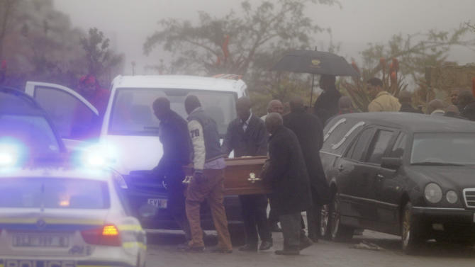 Family members of former South African President Nelson Mandela carry a coffin of a deceased child to be buried near his house in Qunu, South Africa, Thursday, July 4, 2013. In a macabre family feud fought as Nelson Mandela remained in critical condition, a South African court ruled Wednesday that the former president's grandson must return the bodies of the 94-year-old's three deceased children to their original burial site. (AP Photo/Schalk van Zuydam)