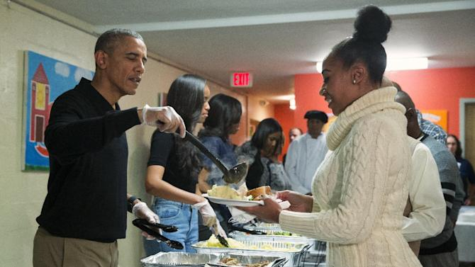"President Barack Obama, from left, Malia Obama, and first lady Michelle Obama serve Thanksgiving dinner during ""Feast with Friends"" at Friendship Place homeless center, on Wednesday, Nov. 25, 2015, in Washington. Friendship Place works with homeless and at-risk veterans in its Veterans First program. (AP Photo/Evan Vucci)"