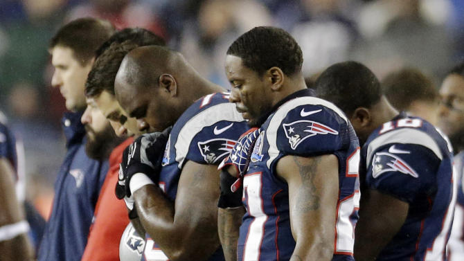New England Patriots defensive tackle Vince Wilfork, left, and strong safety Tavon Wilson, right, join teammates during a moment of silence for the victims of the Sandy Hook Elementary School shootings in Newtown, Conn., before an NFL football game against the San Francisco 49ers in Foxborough, Mass., Sunday, Dec. 16, 2012. (AP Photo/Elise Amendola)