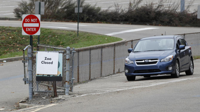 A sign indicating the zoo is closed is seen next to a car with a security guard at the entrance to the parking lots for the Pittsburgh Zoo and PPG Aquarium on Monday, Nov. 5, 2012, in Pittsburgh. Zoo officials said a young boy was killed after he fell into the exhibit that was home to a pack of African painted dogs, who pounced on the boy and mauled him on Sunday, Nov. 4, 2012. It's not yet clear whether the boy died from the fall or the attack, said Barbara Baker, president of the Pittsburgh Zoo & PPG Aquarium. (AP Photo/Keith Srakocic)