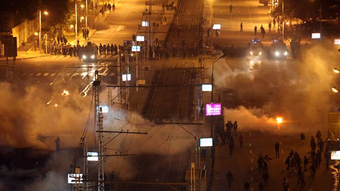 Egyptian security police fire tear gas at protesters during clashes next to the presidential palace in Cairo, Egypt, Friday, Feb. 8, 2013. Egypt has witnessed a fresh cycle of violence over the past two weeks since the second anniversary of the 2011 uprising that deposed longtime autocrat Hosni Mubarak, with clashes across the country having left scores dead and hundreds injured. (AP Photo/Khalil Hamra)