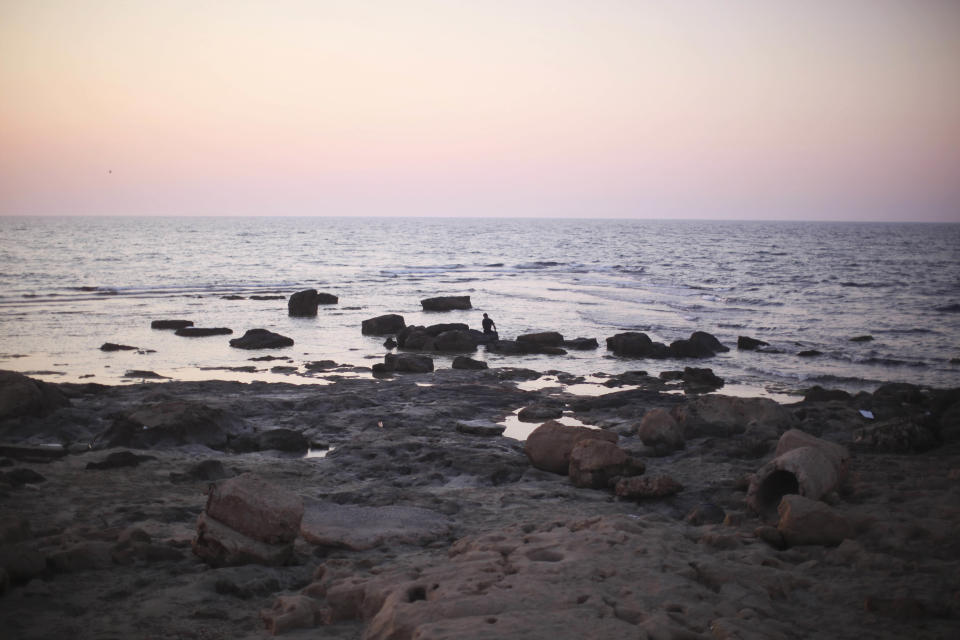 A man rests over rocks at the seaside of the rebel-held town of Benghazi, Libya, Thursday, Aug. 18, 2011. (AP Photo/Alexandre Meneghini)