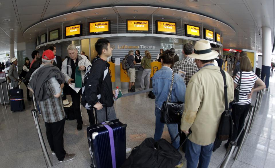 Passengers wait in front of Lufthansa counters as flight attendants of German Lufthansa airline went on an 24-hour-strike for higher wages at the airport in Munich, southern Germany, on Friday, Sept. 7, 2012. (AP Photo/Matthias Schrader)