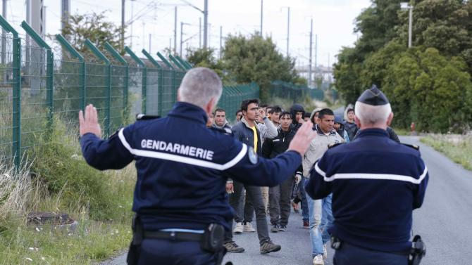 French gendarmes block migrants along a road to prevent them access to train tracks which lead to the Channel Tunnel in Frethun, near Calais