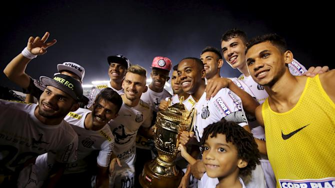 Santos soccer players celebrate with the Sao Paulo state championship trophy after their team defeated Palmeiras in their final soccer match in Santos