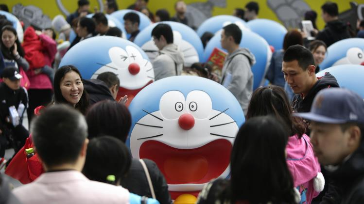 Visitors walk among Doraemon models during an exhibition in Beijing