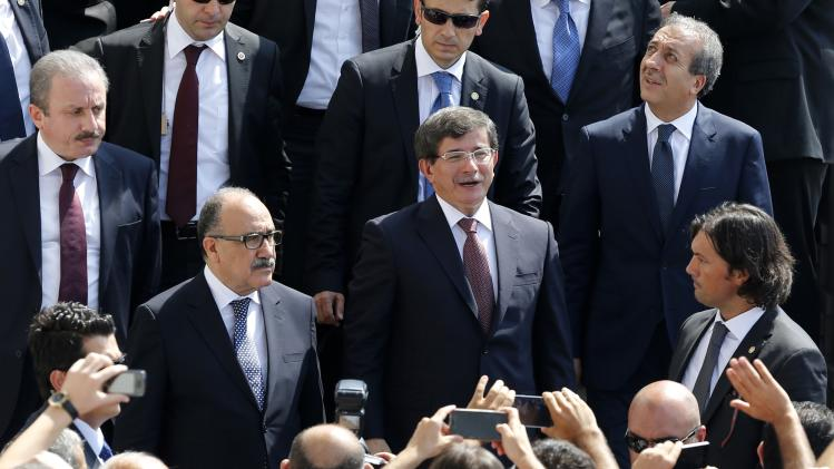 Turkish Prime Minister Ahmet Davutoglu greets his supporters as he leaves Kocatepe Mosque after Friday prayers in Ankara