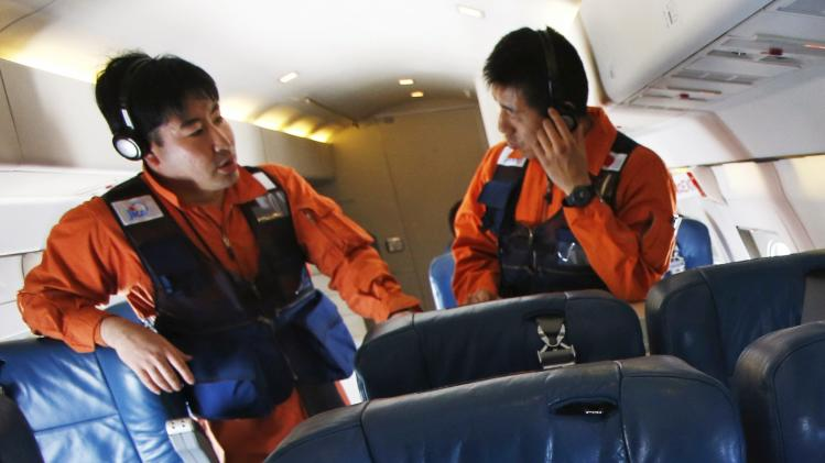 Crew members discuss after search operations for Malaysian Airlines flight MH370 were suspended, over the waters of South China Sea