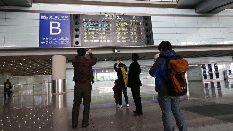 People take pictures of a flight information board displaying the details of Malaysia Airlines flight MH370 at the Beijing Capital International Airport