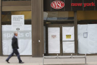 In this Thursday, Feb. 7, 2013 photo, a pedestrian walks past the shuttered New York Sports Club on Water St. in New York. Nearly four months after Superstorm Sandy hit, the historic cobblestone streets near the water&#39;s edge in lower Manhattan are eerily deserted, and among local business owners, there is a pervasive sense that their plight has been ignored by the rest of Manhattan. (AP Photo/Mary Altaffer)