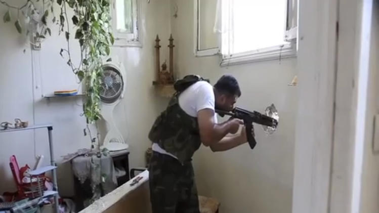 In this image made from video and accessed Saturday, Sept. 1, 2012, a Free Syrian Army fighter fires his weapon at a Syrian Army position through a hole in an empty and destroyed home during fighting in Aleppo, Syria. Syrian troops bombarded the northern city of Aleppo Saturday with warplanes and mortar shells as soldiers clashed with rebels in different parts of Syria's largest city, activists said. The Britain-based Syrian Observatory for Human Rights said the clashes were concentrated in several tense neighborhoods where some buildings were damaged and a number of people were wounded. (AP Photo via AP video)
