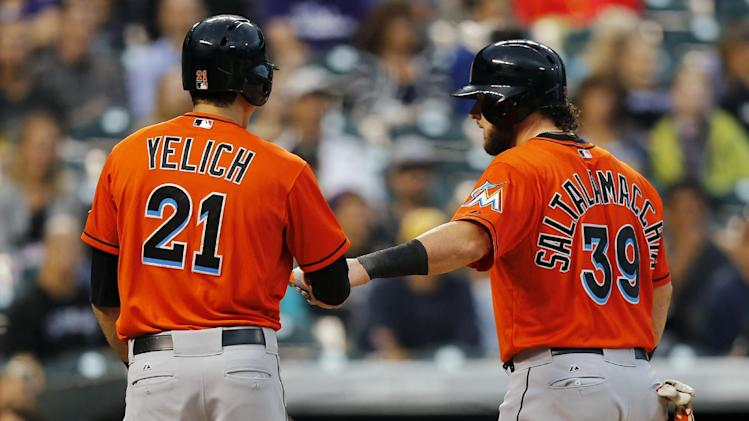 Miami Marlins' Jarrod Saltalamacchia (39) is congratulated by Christian Yelich (21) after scoring on a Henderson Alvarez sacrifice fly against the Colorado Rockies during the second inning of a baseball game Friday, Aug. 22, 2014, in Denver. (AP Photo/Jack Dempsey)