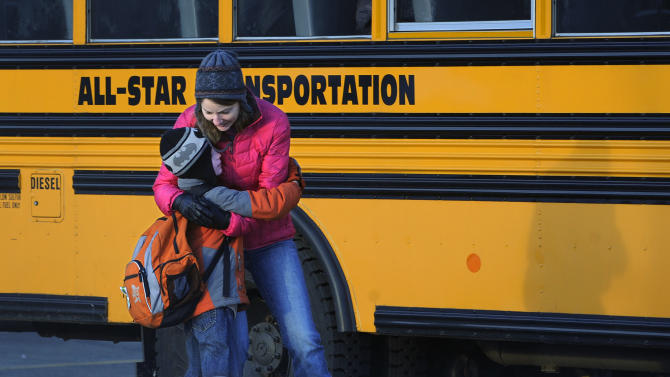 A woman hugs a child before he boards a bus on the first day of classes after the holiday break, in Newtown, Conn., Wednesday, Jan. 2, 2013.    Children from Sandy Hook Elementary School will return to school Thursday in the neighboring town of Monroe.  (AP Photo/Jessica Hill)