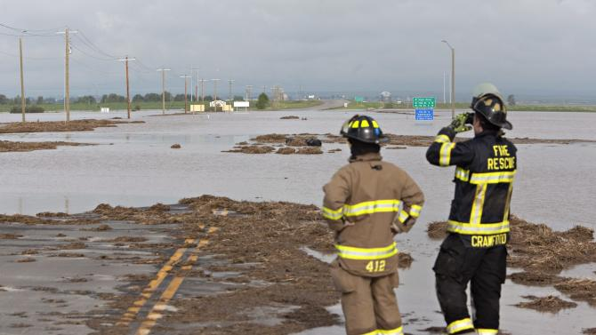 Firefighters monitor flood waters that spilled over a highway 543 north of High River, Alberta, Canada on Friday, June 21, 2013. The rescued passengers spent the night moored on a structure they built in the water. Calgary's mayor said Friday the flooding situation in his city is as under control as it can be, for now. Officials estimated 75,000 people have been displaced in the western Canadian city. Mayor Naheed Nenshi said the Elbow River, one of two rivers that flow through the southern Alberta city, has peaked. (AP Photo/The Canadian Press, Jordan Verlage)