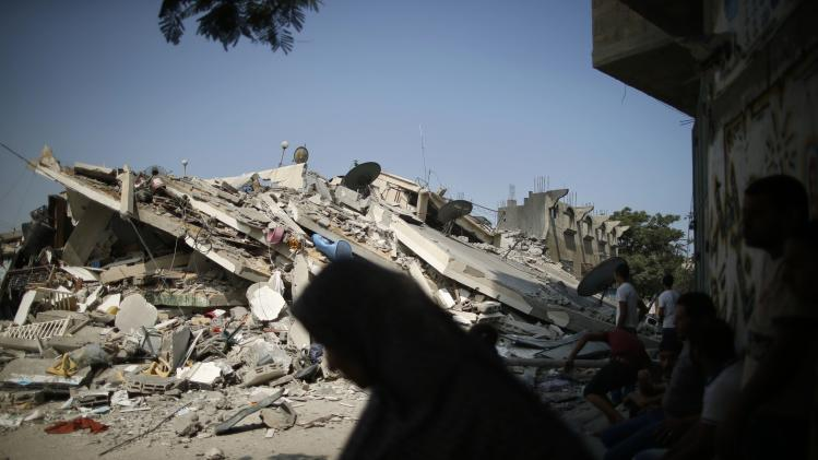 Palestinians look at the rubble of a residential building, which police said was destroyed in an Israeli air strike, in Gaza City