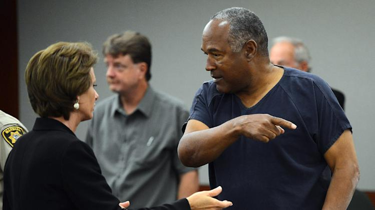 O.J. Simpson, right, talks to his defense attorney Patricia Palm during a break in the second day of  an evidentiary hearing in Clark County District Court, Tuesday, May 14, 2013 in Las Vegas.  The hearing is aimed at proving Simpson's trial lawyer, Yale Galanter,  had conflicted interests and shouldn't have handled Simpson's case. Simpson is serving nine to 33 years in prison for his 2008 conviction in the armed robbery of two sports memorabilia dealers in a Las Vegas hotel room.  Judge Linda Marie Bell let Simpson have one hand unshackled to drink water and take notes.  His left hand was still cuffed to the arm of his chair during the hearing. (AP Photo/Ethan Miller, Pool)