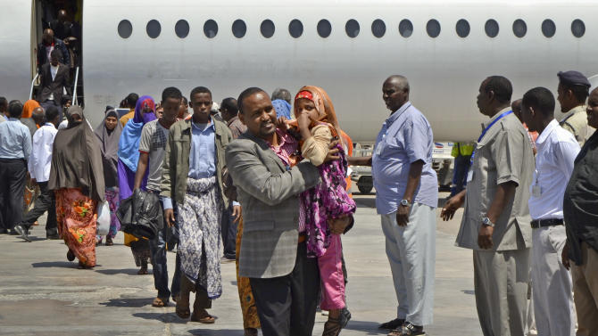 Somali Member of Parliament Muse Sheikh Omar, center, carries a young Somali girl deportee as he helps Somalis who had been deported from Kenya to Somalia from their aircraft after it landed at the airport in Mogadishu, Somalia, Wednesday, April 9, 2014. Kenya's security minister said Wednesday that 82 Somali nationals have been deported in an ongoing security crackdown following recent terror attacks in Kenya's capital and the port city of Mombasa. (AP Photo/Farah Abdi Warsameh)