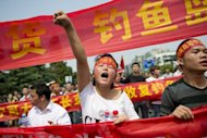 "A demonstrator shouts slogans during a protest against Japan's ""nationalising"" of Diaoyu Islands on Septermber 18 in China. Toyota and Nissan are reducing production in China because demand for Japanese cars has been hit by an island row, officials said Wednesday"