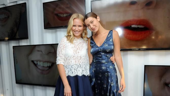 "IMAGE DISTRIBUTED FOR SMILE TRAIN - IMG models Sailor Brinkley Cook, left, and Bella Hadid show off their smiles at the Smile Train multimedia ""When You're Smiling"" installation at Photoville, Thursday, Sept. 18, 2014, at Pier 5 in Brooklyn, New York.   Smile Train is an international children's cleft charity.  (Photo by Diane Bondareff/Invision for Smile Train/AP Images)"
