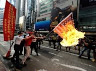 An activist waves a burning Japan-US combined flag during a demonstration over a group of disputed islands known as the Diaoyu Islands in Chinese and the Senkaku Islands in Japanese, in Hong Kong, on September 16