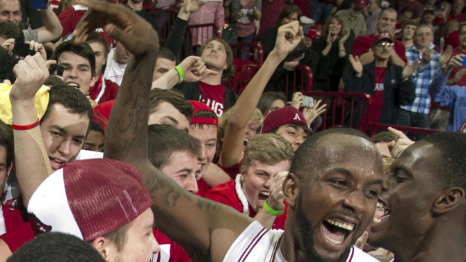 Arkansas' Marshawn Powell, right, celebrates with fans after their 80-69 win over No. 2 Florida in an NCAA college basketball game in Fayetteville, Ark., Tuesday, Feb. 5, 2013. (AP Photo/Gareth Patterson)