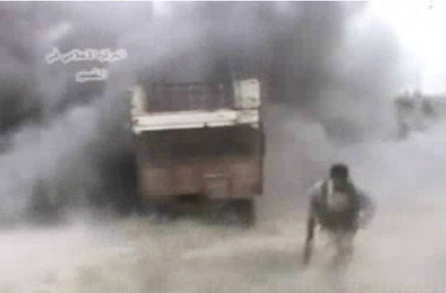 AP10ThingsToSee - In this image from amateur video obtained by a group called Ugarit News, a rebel runs from an explosion, Sunday, May 19, 2013 in Qusair, Syria. An intense battle drove rebels from la