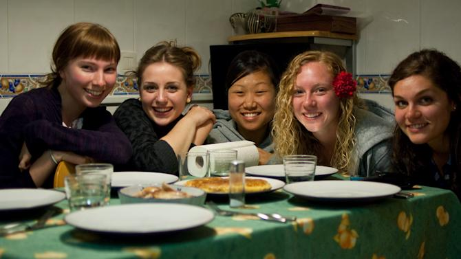 "This March 7, 2010 photo provided by Lauren Hook shows her, left, a new Spanish friend, Carmen Lleo Badal, and other U.S. students Grace Choi, Leah Kosmoski, and Laura Grace Janeskiss before eating a traditional Spanish tortilla omelet at Lleo Badal's family home in Castellon, Spain during the Magdalena Festival. After decades of laissez-faire and faith that just breathing the air in foreign lands broadens horizons, American colleges and international programs are pressing students harder to get out of their comfort zones. ""I noticed a lot of these kids, first time out of the country, all they wanted to do was party,"" said Hook, a University of Georgia senior who spent the spring of 2010 in Spain. The embarrassing sight of fellow Georgia students stumbling drunkenly around Valencia belting out Bulldog fight songs pushed her to explore more on her own. She also appreciated program activities setting up meetings between American students and locals. Meeting a Spanish boyfriend also helped. (AP Photo)"