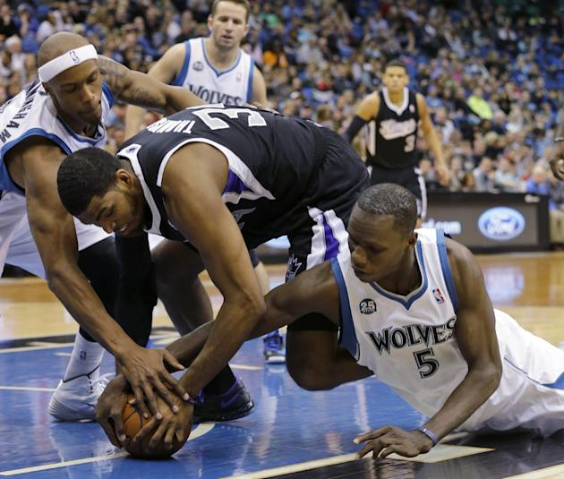 Minnesota Timberwolves forward Dante Cunningham, left, Sacramento Kings forward Jason Thompson, center, and Timberwolves center Gorgui Dieng (5) battle for a loose ball during the second quarter of an