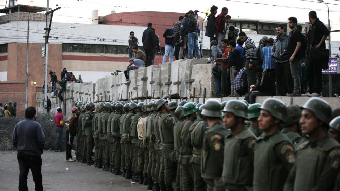 Egyptian army soldiers stand guard as protesters stand on top of cement blocks near the presidential palace in Cairo, Egypt, Sunday, Dec. 9, 2012. Egypt's liberal opposition called for more protests Sunday, seeking to keep up the momentum of its street campaign after the president made a partial concession overnight but refused its main demand he rescind a draft constitution going to a referendum on Dec. 15. (AP Photo/Hassan Ammar)