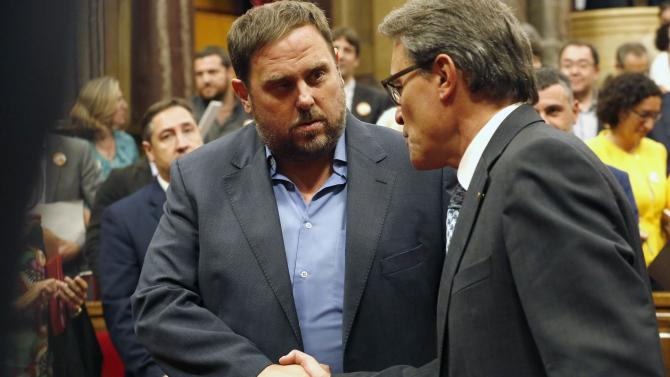 Catalonia's President Mas is congratulated by ERC leader Junqueras after a regional consultation law was approved at Catalonia's Parliament in Barcelona