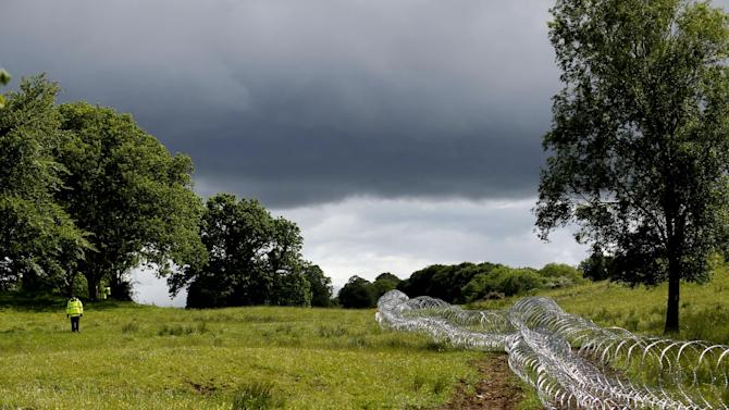 A security person patrols razor wire close to The Lough Erne Golf Resort Enniskillen, Northern Ireland, Thursday, June 13, 2013.  The Resort  is due to host the G8 summit on the 17th and 18th June.  (AP Photo/Peter Morrison)