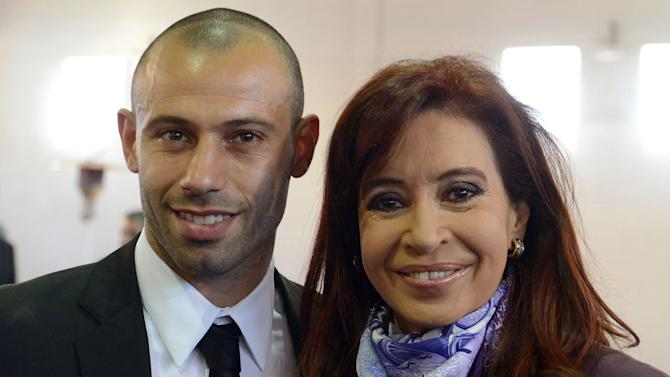 Handout picture released by the Argentine presidency of President Cristina Fernandez de Kirchner (R) posing with Argentina's midfielder Javier Mascherano during their welcoming ceremony from the World Cup where they ended up in second place