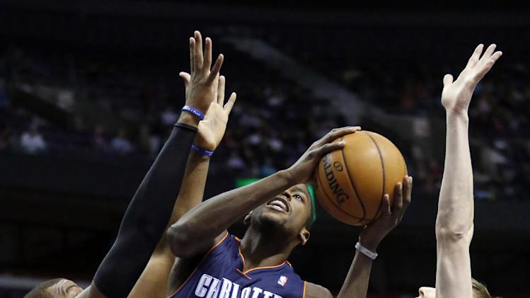 Charlotte Bobcats forward Michael Kidd-Gilchrist (14) goes to the basket between Detroit Pistons center Greg Monroe (10) and forward Kyle Singler (25) in the first half of an NBA basketball game, Sunday, Jan. 6, 2013, in Auburn Hills, Mich. (AP Photo/Duane Burleson)