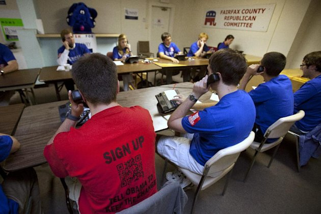 Allen Luethky, 19, left, of Oakton Va., makes calls for the Romney campaign while wearing a t-shirt featuring a quick response code, or QR, in Fairfax, Va., on Tuesday, June 19, 2012. The presidential ground game has gone high tech, marrying old-school organizing work with innovative digital tools. The T-shirts that Romney campaign volunteers wear in Virginia feature a digital code that voters can zap with their smart phones to learn more about the Republican presidential hopeful, which gives Romney field organizers valuable information on how to reach them in the future. (AP Photo/Jacquelyn Martin)