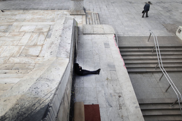 FILE -  In this Tuesday, Jan. 22, 2013 file photo, a homeless man sits near the closed entrance of a Metro station in central Syntagma square during a strike held by the unions of metro services in At
