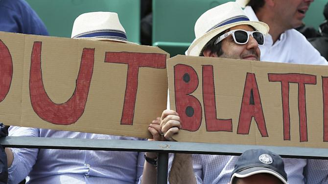 """Two spectators hold signs reading """"Out Blatter"""", referring to newly re-elected FIFA president Sepp Blatter during the quarterfinal match of the French Open tennis tournament between Spain's Garbine Muguruza and Lucie Safarova of the Czech Republic at the Roland Garros stadium, in Paris, France, Tuesday, June 2, 2015. Blatter said Tuesday he will resign from his position amid corruption scandal. (AP Photo/David Vincent)"""