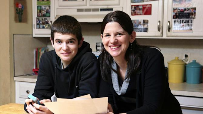 In this Jan. 4, 2013, photo, Janell Burley Hofmann, right, poses with her son Gregory at their home in Sandwich, Mass. Janell holds a copy of the contract she drafted and that Gregory signed as a condition for receiving his first Apple iPhone. (AP Photo/Michael Dwyer)
