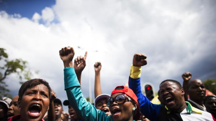 Frustrated mourners shout slogans behind police cordons after being denied entry to the site where former South African President Nelson Mandela was lying in state, in Pretoria