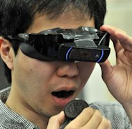 A man eats a cookie with a camera-equipped special goggle develped by a Tokyo University professor. The equipment makes cookies bigger to help users' diet. (AFP Photo/Yoshikazu Tsuno)