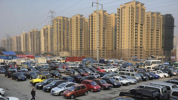 Car dealers and customers walk at a second-hand car market in Hefei