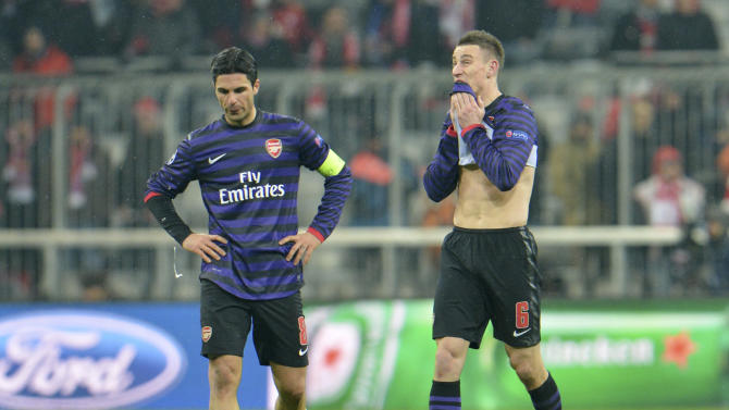 Arsenal's Mikel Arteta, left, and Laurent Koscielny react after the Champions League round of 16 second leg soccer match between FC Bayern Munich and FC Arsenal in Munich, Germany, Wednesday, March 13, 2013. (AP Photo/Kerstin Joensson)