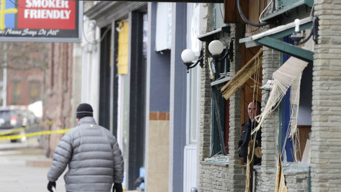 Law enforcement officials work at the building where a man was killed after police stormed it following a standoff on, Thursday, March 14, 2013, in Herkimer, N.Y. The man was suspected of two shootings on Wednesday that killed four and injured two others. (AP Photo/Mike Groll)