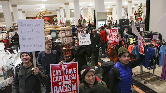 Black Lives Matter protesters walk through a Macy's store on Black Friday in Seattle, Washington